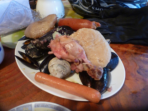 A single serving of Curanto, a traditional Chilota dish that was usually prepared in the ground with hot rocks, but is now more often prepared in a huge dish and even includes completos (= hot dogs).  Quemchi, Chiloé