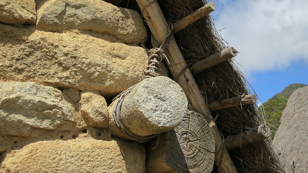 These round, timber-looking stones protruded near the roof line on many structures.  The rebuilt houses show the roofs being tied off to them (as pictured).  Maybe these stone builders just liked the exotic timber frame look?